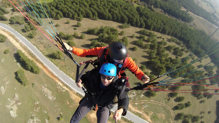 skydive: Tourist playing paragliding guided by a pilot