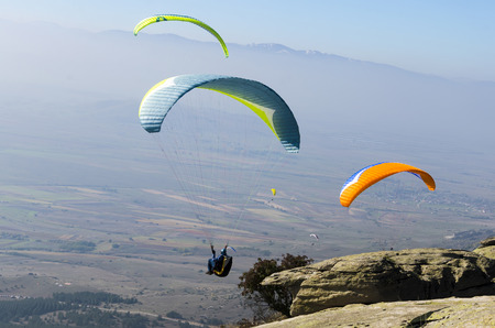 Three paragliders fly at day blue sky