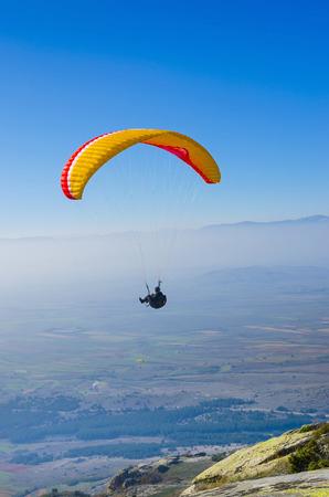 hang glider: orange paraglider on the blue sky