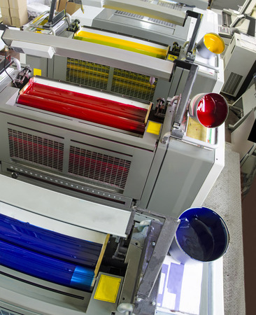 imprenta: cilindros de máquinas de impresión y bote de tinta de impresión con color amarillo rojo cian