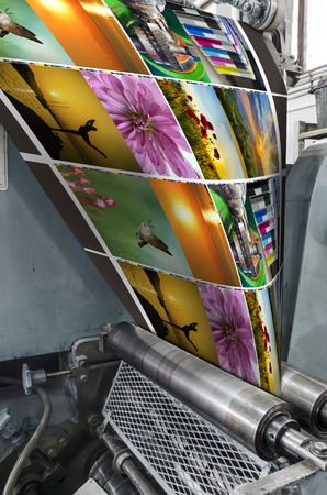 Large webset offset printing press running a long roll off paper over its rollers at high speed. VERTICAL