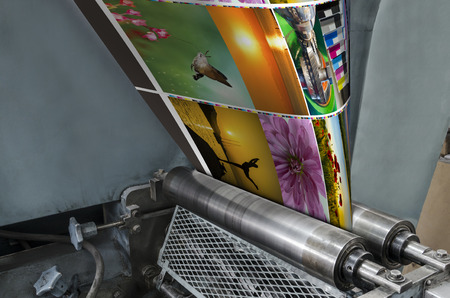 printing inks: Large webset offset printing press running a long roll off paper over its rollers at high speed.