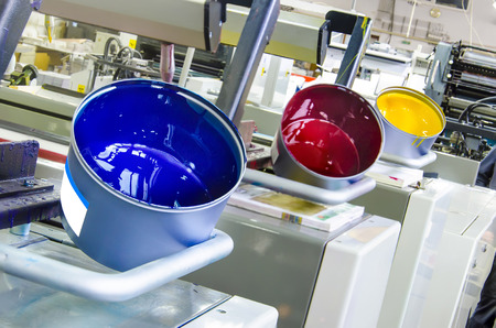 cmyk: printing machine cylinders and printing ink pot with cyan red yellow color