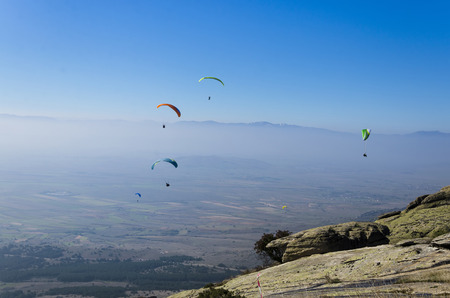 adrenaline: Paragliders at clear blue sky. Paragliding is extreme adrenaline sport. Stock Photo