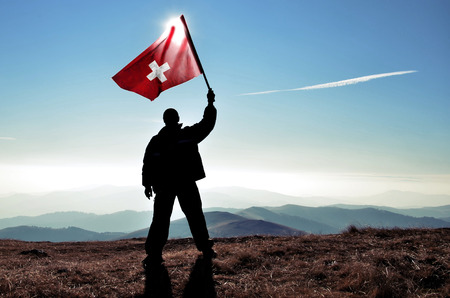 switzerland flag: successful silhouette man winner waving Swiss flag on top of the mountain peak