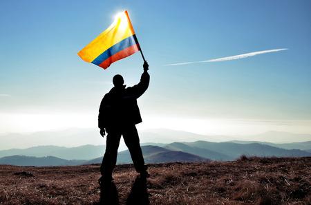 columbian: successful silhouette man winner waving Columbian flag on top of the mountain peak