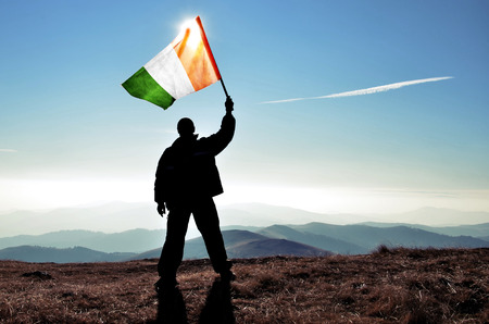 successful silhouette man winner waving Ireland flag on top of the mountain peak Фото со стока