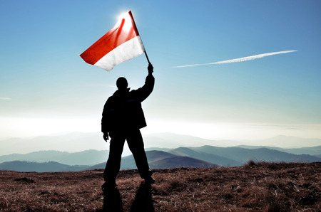 the indonesian flag: successful silhouette man winner waving Indonesia flag on top of the mountain peak Stock Photo