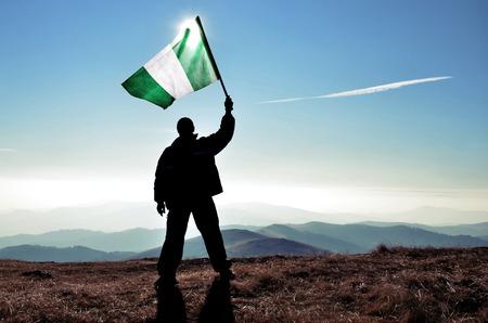 山のピークの上にナイジェリアの旗を振って成功シルエット男優勝