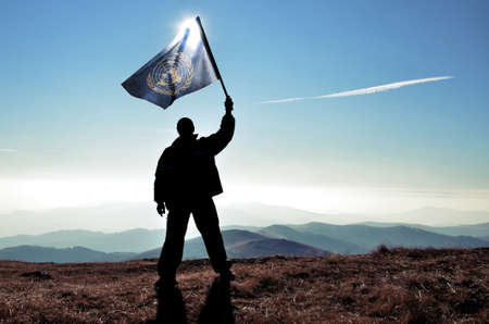 un: successful silhouette man winner waving UN flag on top of the mountain peak