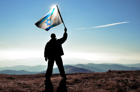 flag of israel: successful silhouette man winner waving Israel flag on top of the mountain peak Stock Photo