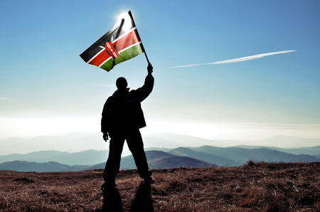 successful silhouette man winner waving Kenya flag on top of the mountain peak Фото со стока - 41934313