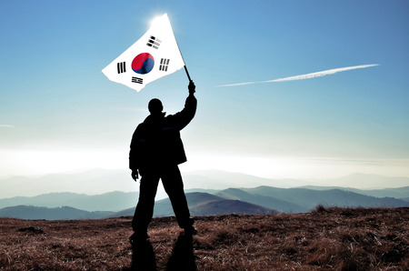 the concept of independence: successful silhouette man winner waving South Korea flag on top of the mountain peak Stock Photo