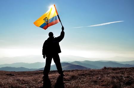 에콰도르 플래그를 산 꼭대기에 흔들며 성공적인 실루엣 남자 우승자 스톡 콘텐츠