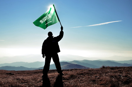 winner: successful silhouette man winner waving Saudi Arabia flag on top of the mountain peak Stock Photo