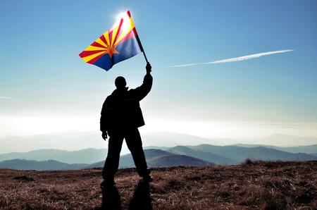 successfull: successfull silhouette man winner waving Arozona flag on top of the mountain peak Stock Photo