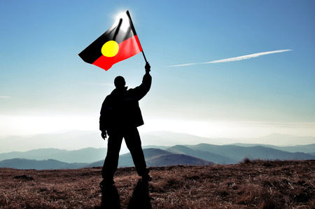 successfull: successfull silhouette man winner waving Australian Aborigean flag on top of the mountain peak