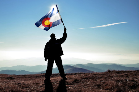 successfull silhouette man winner waving Colorado flag on top of the mountain peak 스톡 콘텐츠