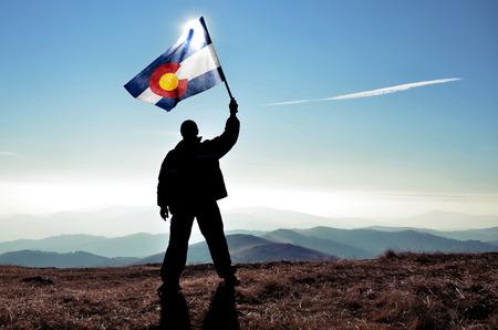 successfull silhouette man winner waving Colorado flag on top of the mountain peak Standard-Bild