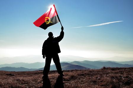 successfull: successfull silhouette man winner waving Angola flag on top of the mountain peak Stock Photo