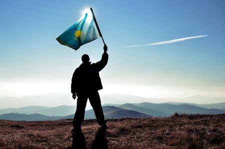 successfull: successfull silhouette man winner waving Kazakhstan flag on top of the mountain peak