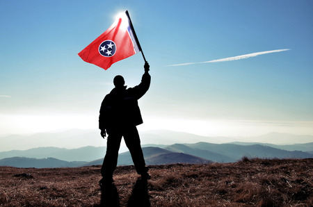 successfull: successfull silhouette man winner waving Tennessee flag on top of the mountain peak