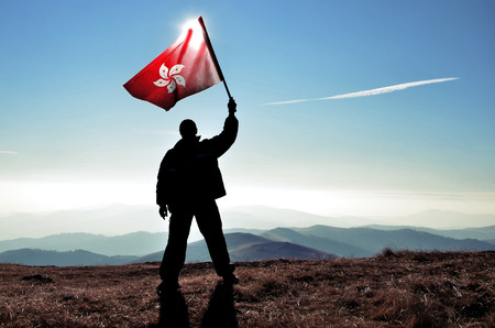successfull silhouette man winner waving Hong Kong flag on top of the mountain peak Stock Photo