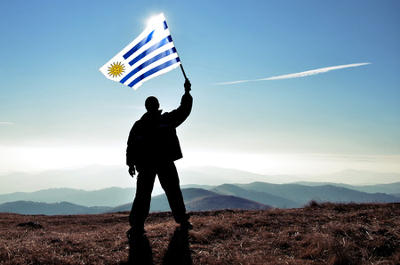 bandera de uruguay: ganador de la silueta del hombre exitoso que agita la bandera Uruguay en la parte superior del pico de la montaña