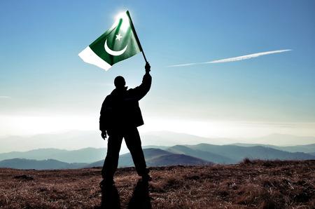 successfull: successfull silhouette man winner waving Pakistan flag on top of the mountain peak