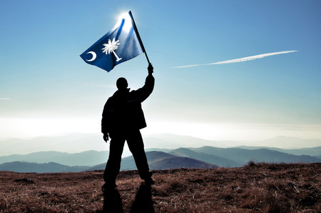 summits: successfull silhouette man winner waving South carolina flag on top of the mountain peak