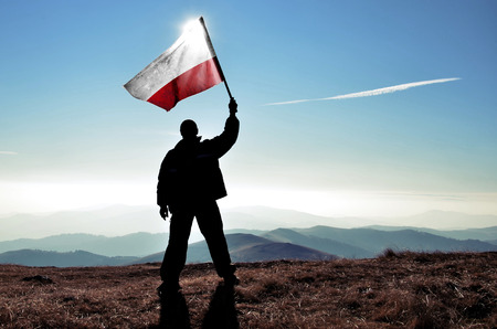 successfull silhouette man winner waving Polish flag on top of the mountain peak 스톡 콘텐츠
