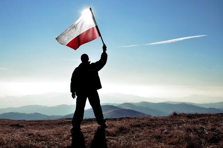 bandera de polonia: ganador silueta del hombre exitoso que agita la bandera polaca en la parte superior del pico de la montaña
