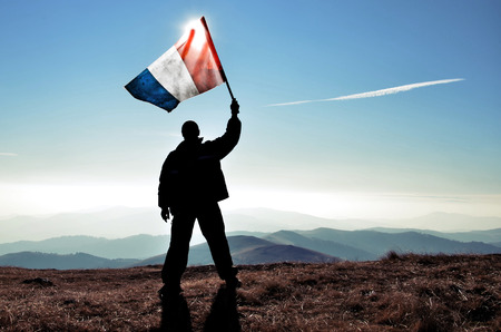 successfull silhouette man winner waving French flag on top of the mountain peak Фото со стока - 41934342