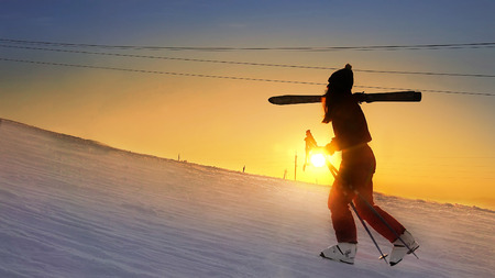Ski girl climb the slope at winter sunset snow