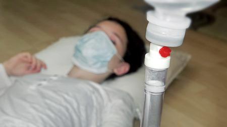 intravenous: Intravenous saline drip with child patient face out of focus