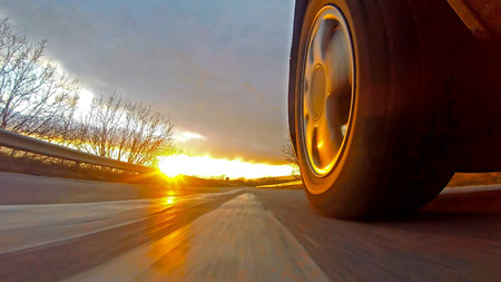 Driving a sport car on a country road at sunset. Wheel spinning POV - Point of View. Fast Speed Stock Photo