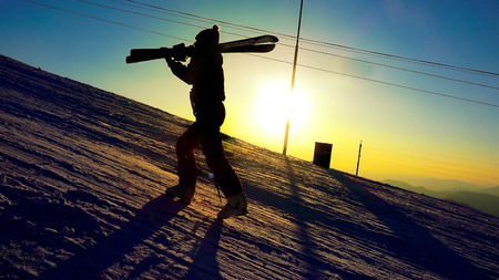 freeride: Silhouette of a woman with ski in winter mountains sunset close up Stock Photo