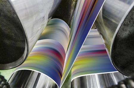 Una prensa de impresión offset grande que ejecuta un largo rollo de papel sobre sus rodillos a alta velocidad Foto de archivo
