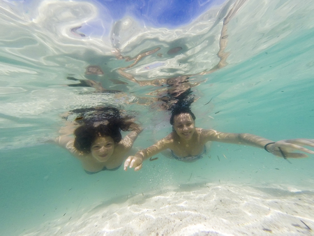 flippers: Smiling girls swimming underwater in sea with clear water and sand bottom