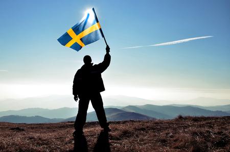 bandera de suecia: Successful silhouette man winner waving Sweden flag on top of the mountain peak