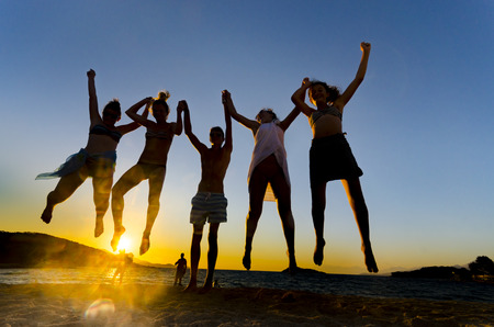 Happy funny people jumping in the sunset on the beach