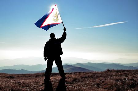 winner man: Successful silhouette man winner waving American Samoaman flag on top of the mountain peak