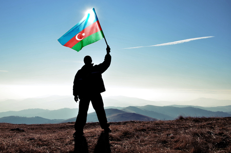 azerbaijanian: Successful silhouette man winner waving Azerbaijan flag on top of the mountain peak