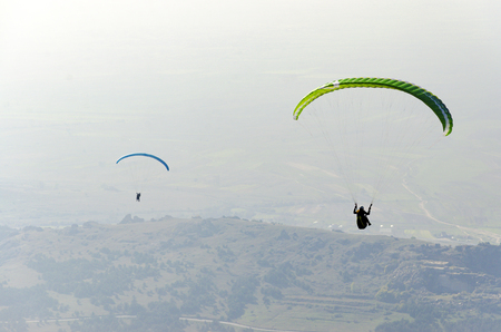 Paragliders silhouette flying over misty mountain valley - sport, active wallpapers full of freedom