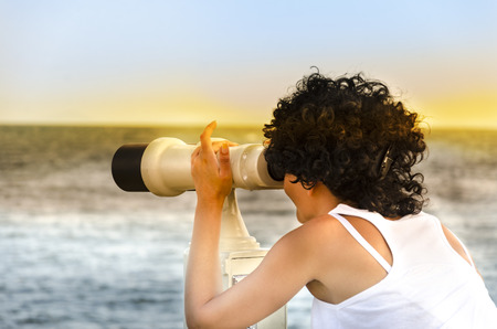 Girl with a telescope on the observation platform tourist at sunset Stock Photo