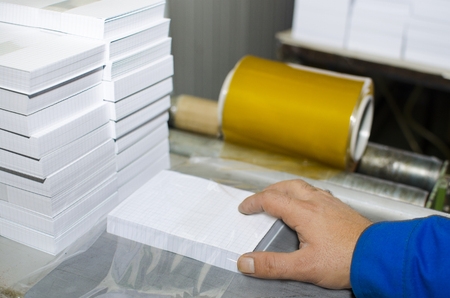Workers in printing house. Packaging stuck of notebook paper. Industrial workers