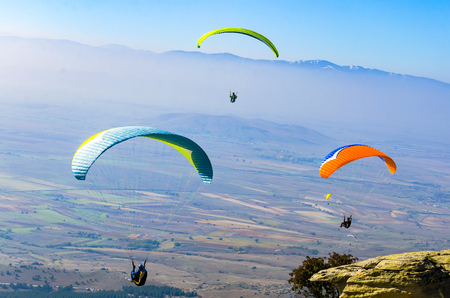PRILEP, MACEDONIA - circa FEB, 2017: Three paraglider flies paraglider over the tops of the mountains in summer sunny day Editorial