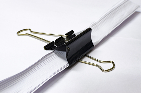 black paper clip holds stack of white print paper, office concept background, selective focus