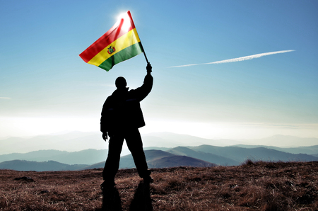 conquest: Successful silhouette man winner waving Bolivia flag on top of the mountain peak