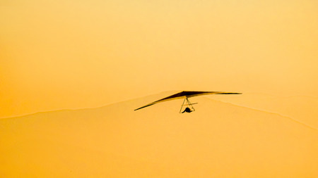 high powered: Hang glider silhouette flying at sunset Stock Photo